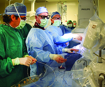 From left, USC faculty physicians David Shavelle, Vaughn Starnes and Ray Matthews perform a transcatheter aortic valve implantation in a new hybrid operating room at Keck Hospital of USC. (Photo/Alison Trinidad)