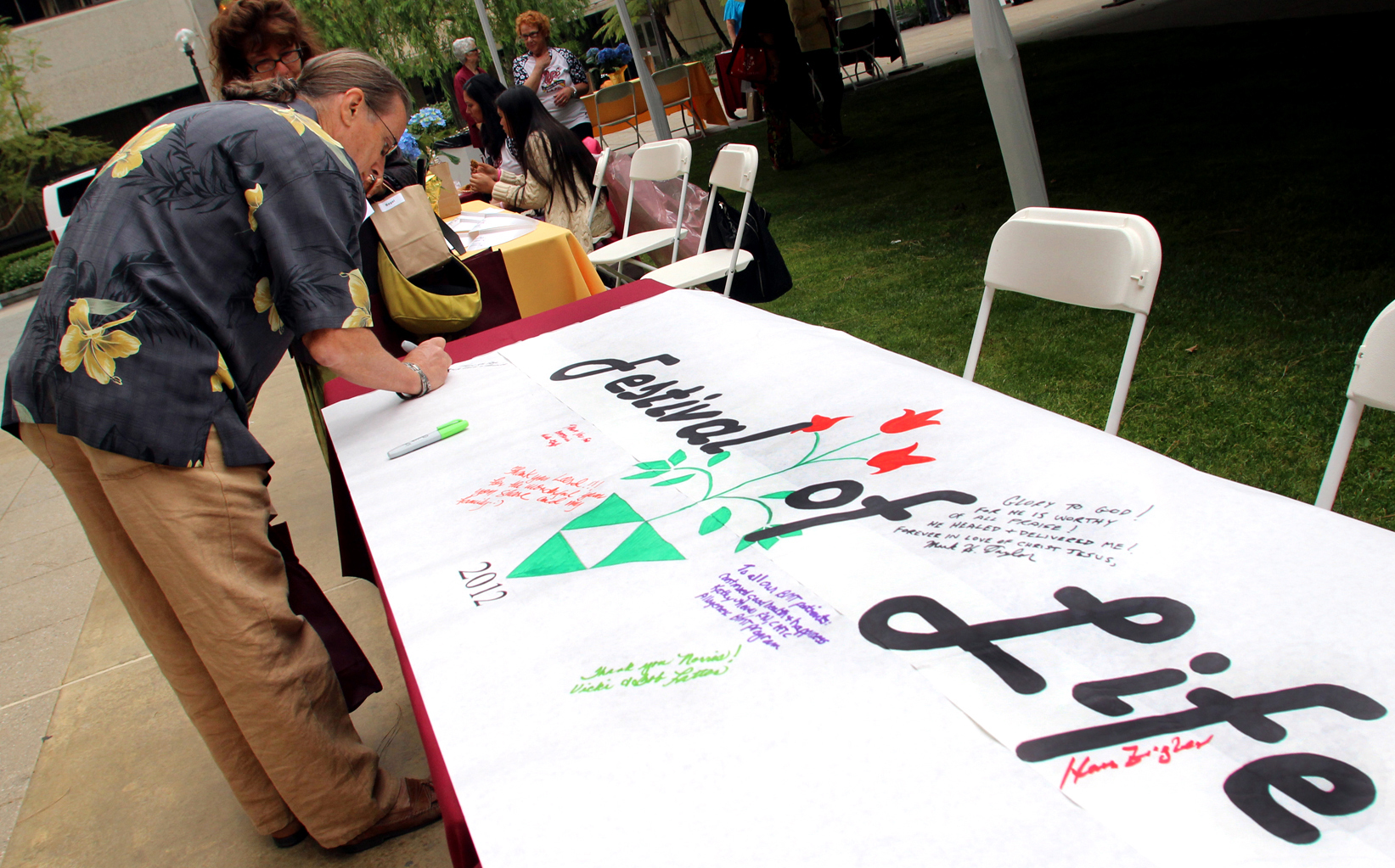 Participant signs a scroll.