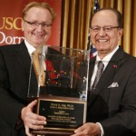 Dean Steve A. Kay accepts a symbolic armchair from USC President C. L. Max Nikias. (Photo/Steve Cohn)