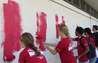 USC students paint a wall at 32nd Street/USC MaST High School during a Friends and Neighbors Service Day. (Photo/Marla Schevker)