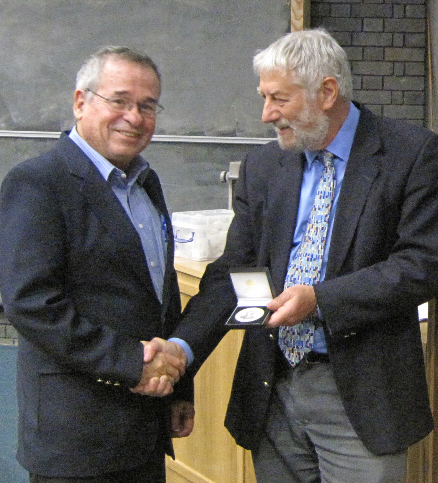 Arieh Warshel, left, receives his 2012 Soft Matter and Biophysical Chemistry Award from Graham Hutchings of the Royal Society of Chemistry during a three-day symposium in England. (Photo/Courtesy of the Royal Society of Chemistry)