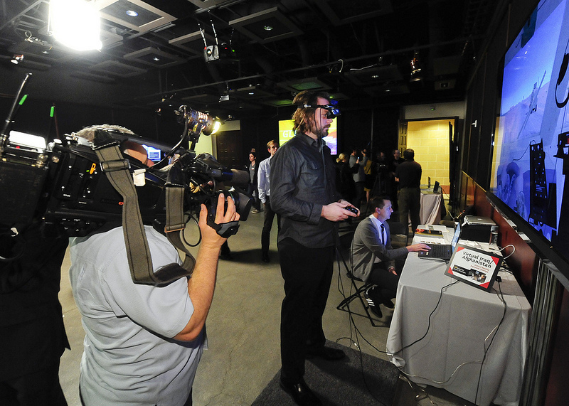 A cameraman from a local affiliate shoots Ryan French from the USC Institute for Creative Technologies as he demonstrates Virtual Iraq/Afghanistan, a virtual reality program designed for PTSD therapy of combat veterans. (Photo/Gus Ruelas)