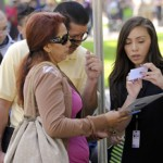 Carmen Andrea Chavez, right, helps Amelia Gonzalez and her husband, Luis, as they line up for seminar vouchers during the Financial Fair at USC. (USC Photo/Gus Ruelas)