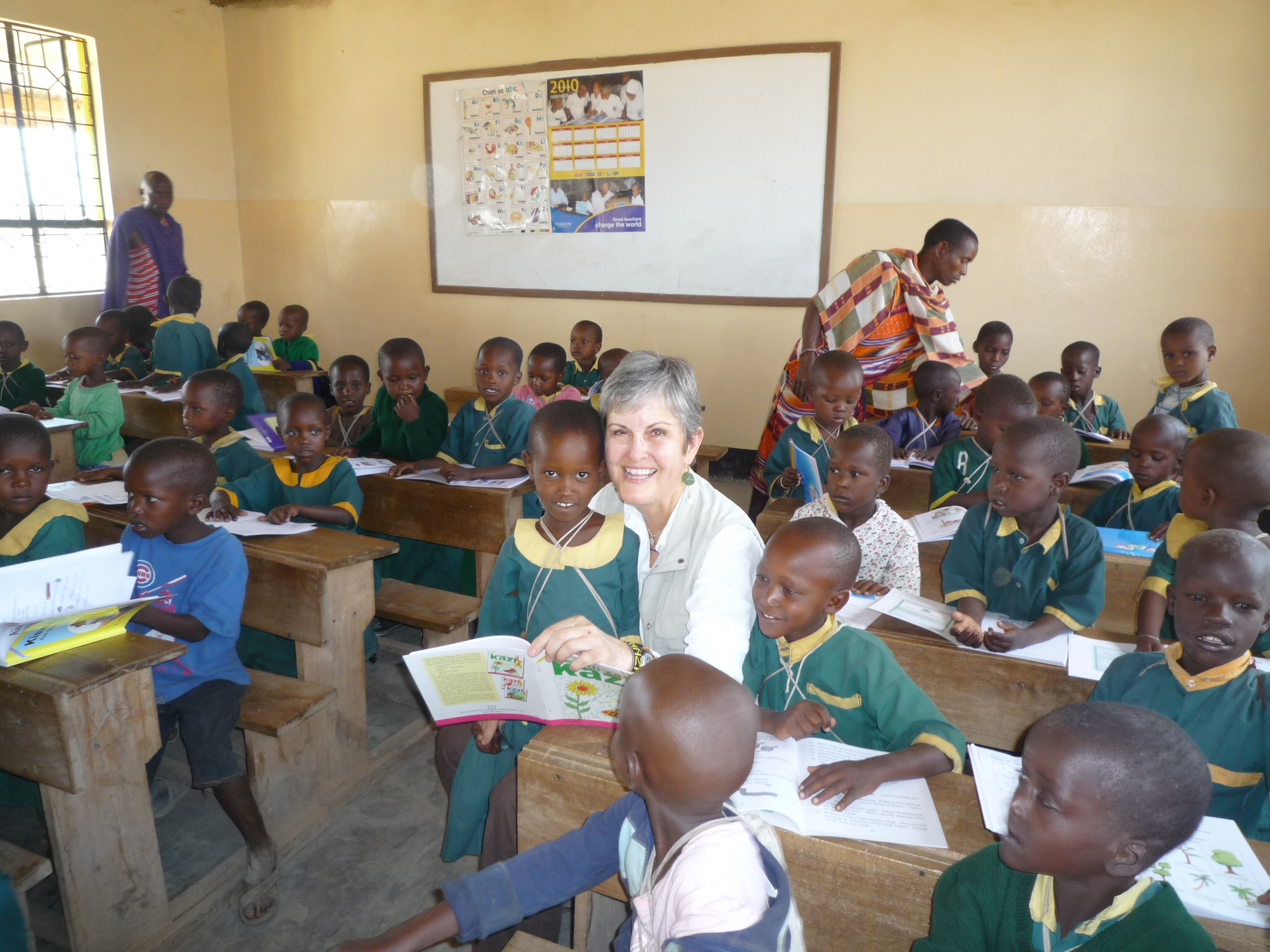 Cheryl Kile sits with students at Endupoto Primary School, which is preparing to build its fifth classroom this year. (Photo/Courtesy of USC Rossier)