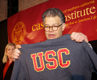 Sen. Al Franken holds a USC sweatshirt after delivering his speech as the 12th annual Carmen and Louis Warschaw Distinguished Lecture. (Photo/Jon Vidar)