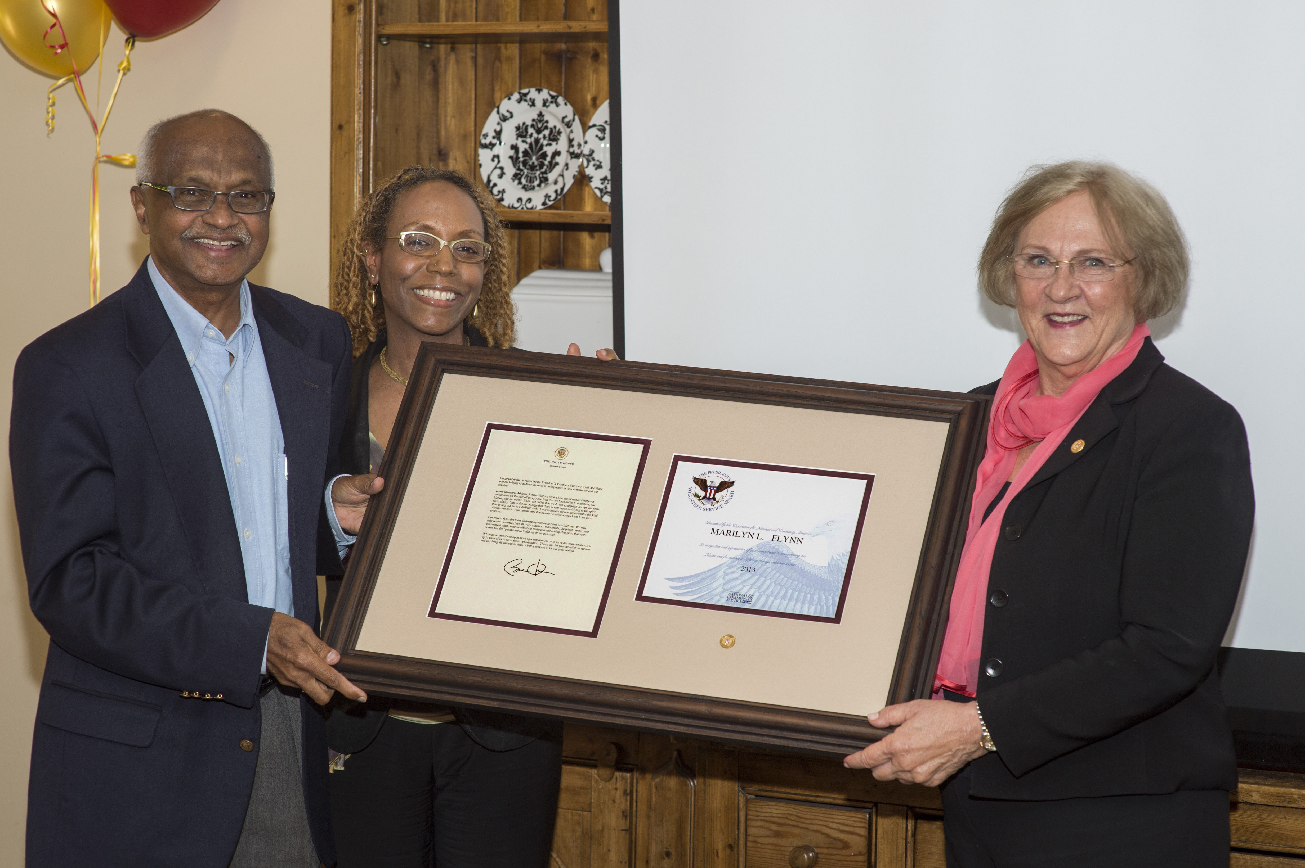 Clinical Professors Murali Nair and Renee Smith-Maddox present the President's Volunteer Service Award to Dean Marilyn L. Flynn. (Photo/Andrew Taylor)