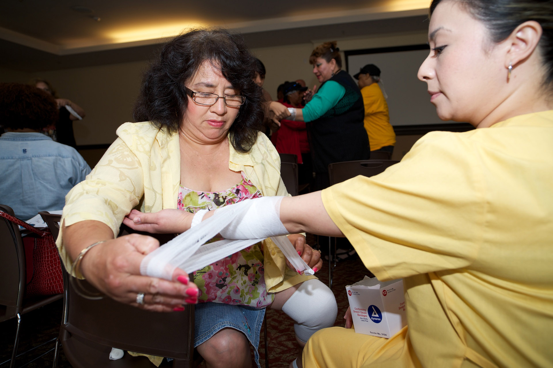 Lilia Garcia and Lizett Esparza practice first aid at a USC Neighbors Emergency Team workshop. (USC Photo/Dietmar Quistorf)