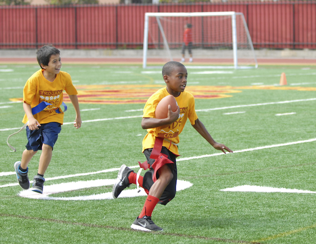 Two boys take part in football drills during Trojan Kids Camp. (USC Photo/Lillian Insalata)