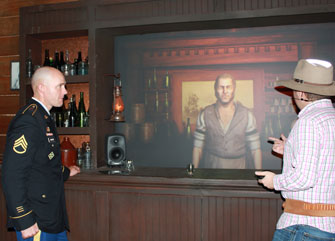 Medal of Honor recipient Ty Michael Carter interacts with virtual bartender Utah Thornton and ICT technical project specialist Jamison Moore in ICT's Gunslinger saloon, an interactive narrative experience and  testbed for virtual human research. (Photo/courtesy of ICT)