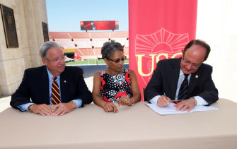 USC President C. L. Max Nikias signs the agreement as Don Knabe and Fabian Wesson look on. (USC Photo/Dietmar Quistorf)