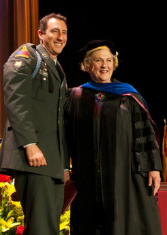 A student veteran celebrates with Dean Marilyn L. Flynn at the USC School of Social Work's 2012 commencement ceremony.