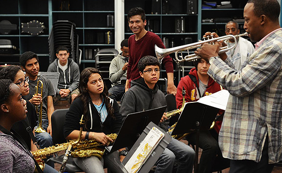 USC Dornsife junior Eduardo Mollinedo-Piñon, standing, co-directs as Foshay Learning Center music director Vincent Womack plays the trumpet during a rehearsal of the Foshay Symphonic Band. (USC Photo/Erica Christianson)