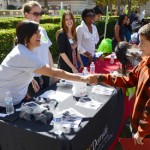 Jasmine Torres greets a young student at the Trojan Guardians Scholarship program booth during a College Within Reach event. (USC Photo/Erica Christianson)