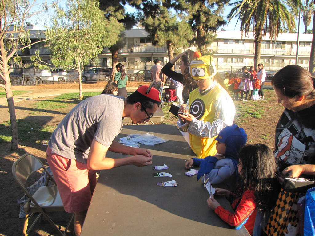 USC Topping scholar Erik Estrada helps neighborhood children craft ghostly magnets. (Photo/Tandia Elijio)