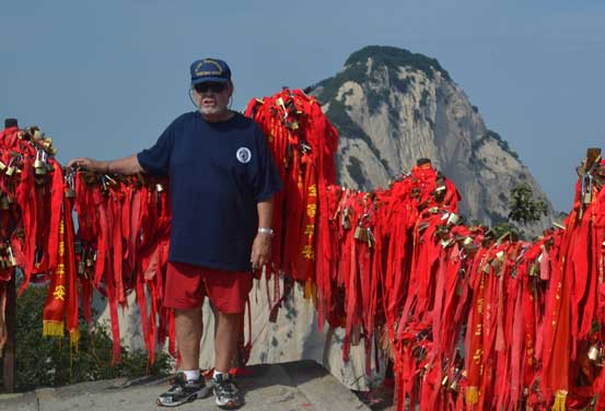 William Altaffer, among the most traveled people in the world, stands at the summit of China's Mount Hua Shan surrounded by red Tibetan Buddhist prayer flags.