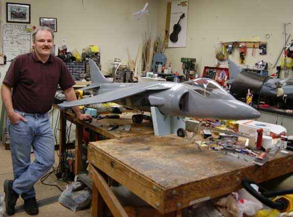 Ewald Schuster, standing next to an earlier version of the Harrier jet, helps students craft and test their aircraft designs at USC Viterbi. (USC Photo/Andrew Good)