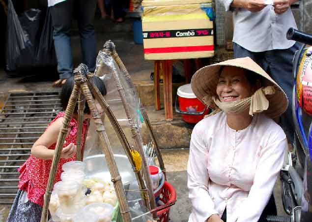 A young customer spends time with a sweets vendor in Ho Chi Minh City