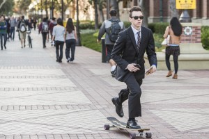 Student on skateboard in suit