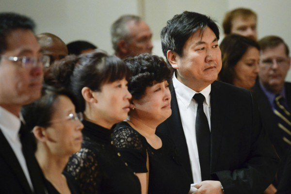 Xinran Ji's family, including father Songbo Ji, right, and Jinhui Dui, second from right, attend a service in memory of their son. (USC Photo/ Gus Ruelas)