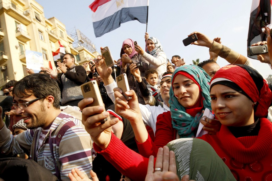 During the Arab Spring, Egyptians used their mobile phones to document unrest and celebrations. (MOHAMMED ABED/AFP/GettyImages)