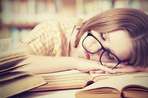 girl with glasses sleeping on the books in the library,