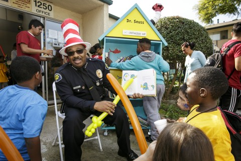 "DPS Chief John Thomas reads a Dr. Seus book to kids during the unveiling of a ""Little Free Library"""