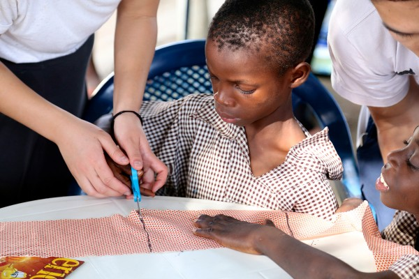 A child learns how to sew. (Photo/Heather Dingess)