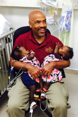 Surgeon Henri Ford relaxes in Haiti with the twins three days after the surgical separation. (Photo/Los Angeles Children's Hospital)