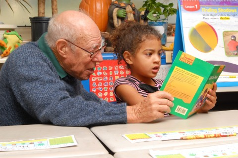 older volunteer reads with child