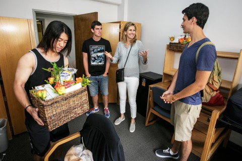 "Mother Katheryn Moseley presents a welcome basket to her son's roommate, Boyuan ""Addison"" Xie, left,  as suite mate Jose Pueyo Poves looks on. (USC Photo/David Sprague)"
