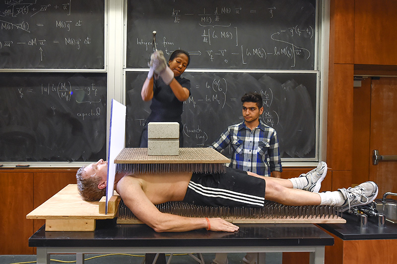 Physics professor Gene Bicker lays on a bed of nails to illustrate to his students a principal of physics, February 10, 2016. (USC Photo/Gus Ruelas)