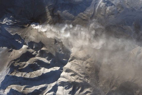 Volcano spewing ash into air