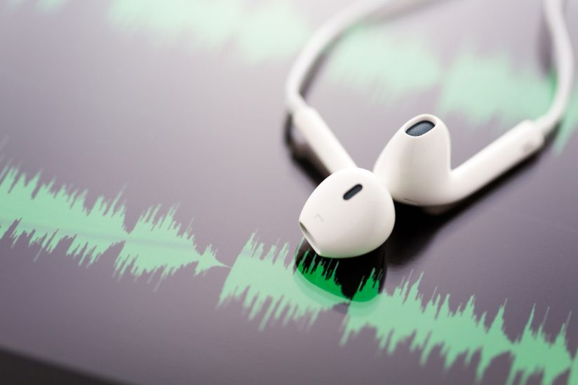white headphones on top of waveforms