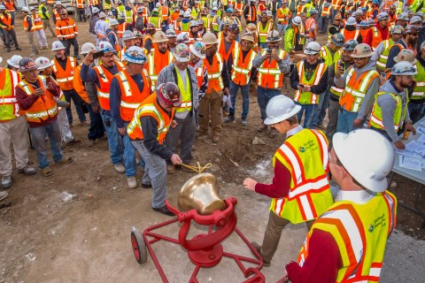 Construction workers gathered to ring victory bell