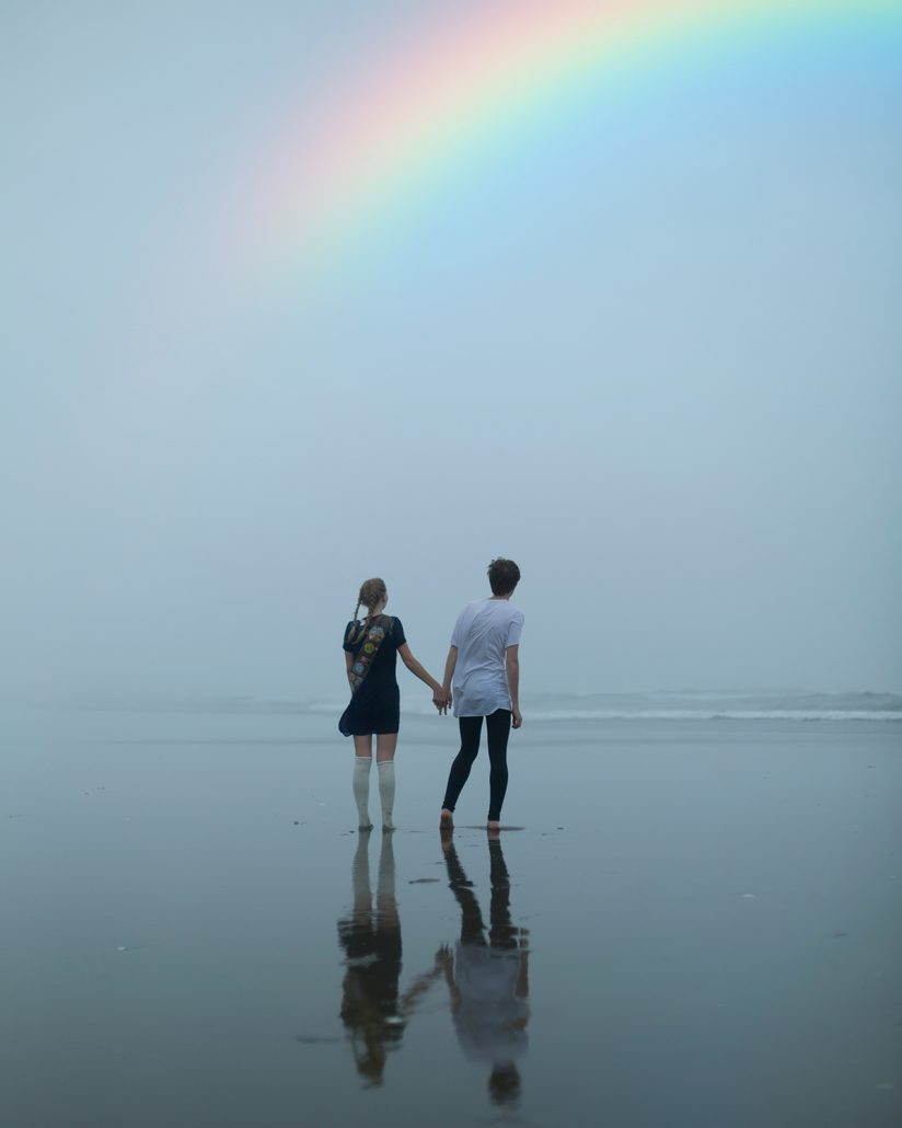 rainbow in cloudy sky over two people holding hands