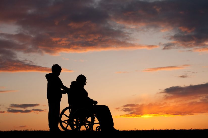 Silhouette of boy pushing man in a wheelchair at sunset
