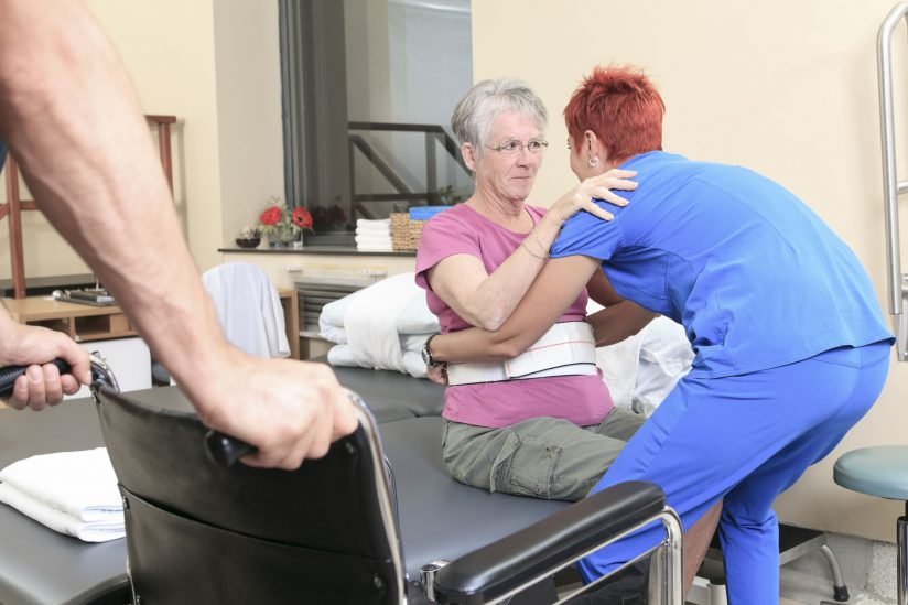 female patient practicing rehabilitation techniques with help of physical therapist
