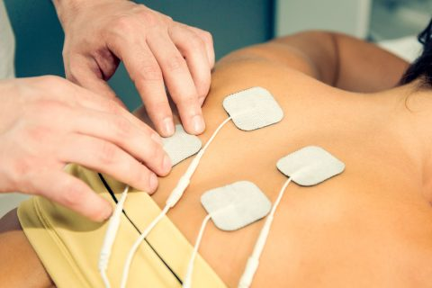 Therapist positing TENS electrodes
