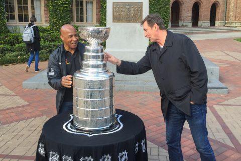 Lynn Swann, Wayne Gretzky look at Stanley Cup near Tommy Trojan