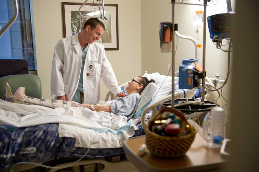 doctor chatting with patient in hospital room
