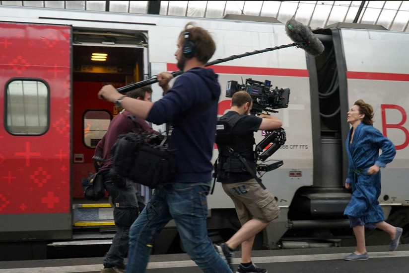 actress running on train platform with film crew