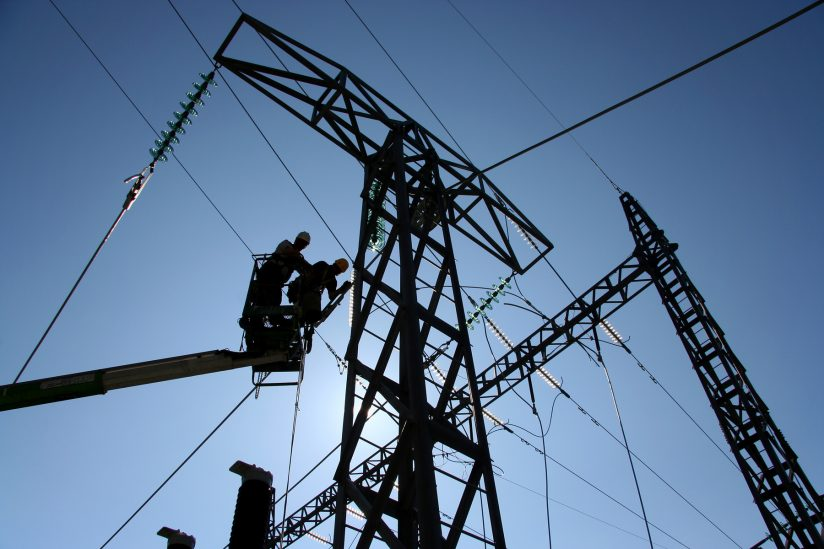 silhoutte of workers on power lines