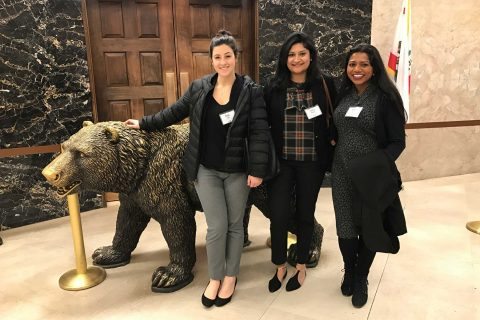 Three students posing next to bear statue in Sacramento
