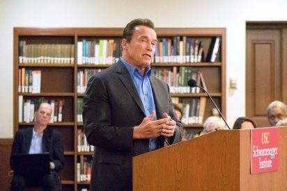 Arnold Schwarzeneggar speaking at podium