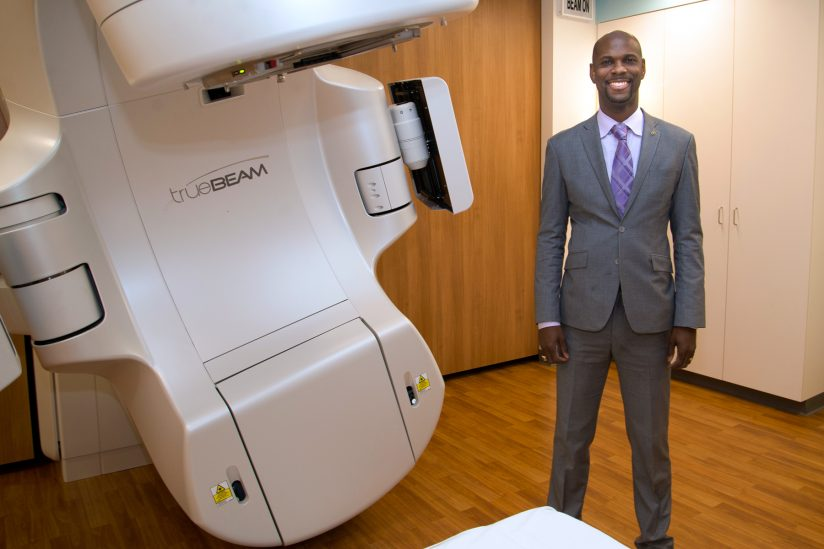 Stonish Pierce in front of radiation treatment equipment at new clinic