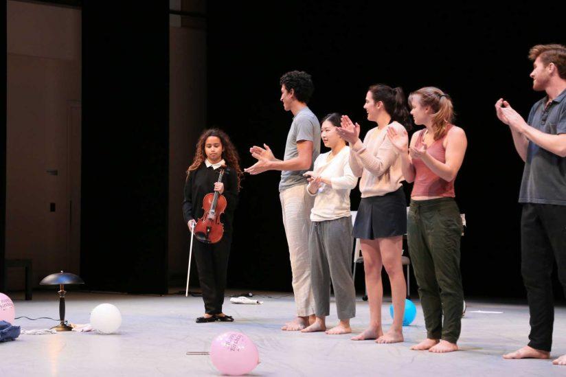Mya Greene onstage with violin applauded by dancers