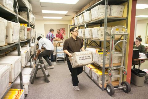 staff carrying container of mail in mail room