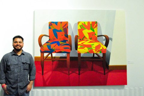Roberto Ortiz next to paintings