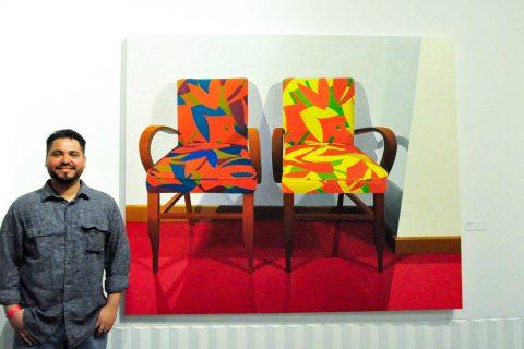 Roberto Ortiz next to paintings