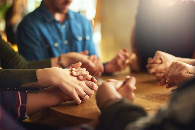 closeup of group holding hands, praying